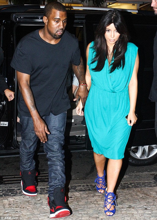 Knight in shining armour: Kanye West gave pregnant Kim Kardashian a helping hand in Brazil on Friday