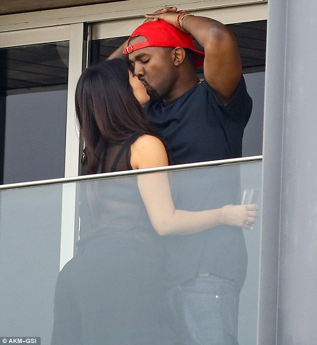 Te amo: Kim Kardashian and Kanye West share a kiss on the blscony of the Fasano hotel in the Rio De Janeiro district of Ipanema