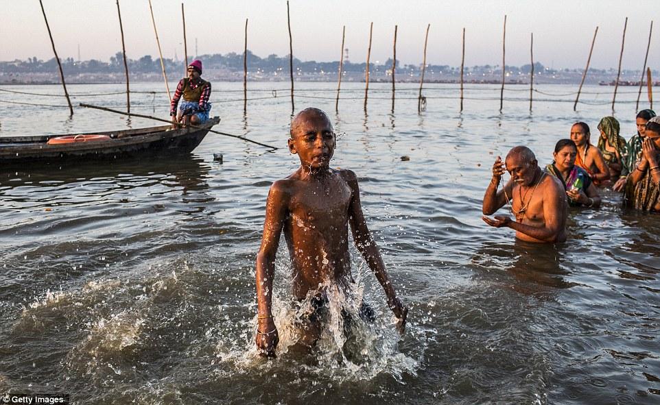 Время, чтобы очистить: мальчик берет провал, как он и другие преданные индуистских купаться на берегу Sangam