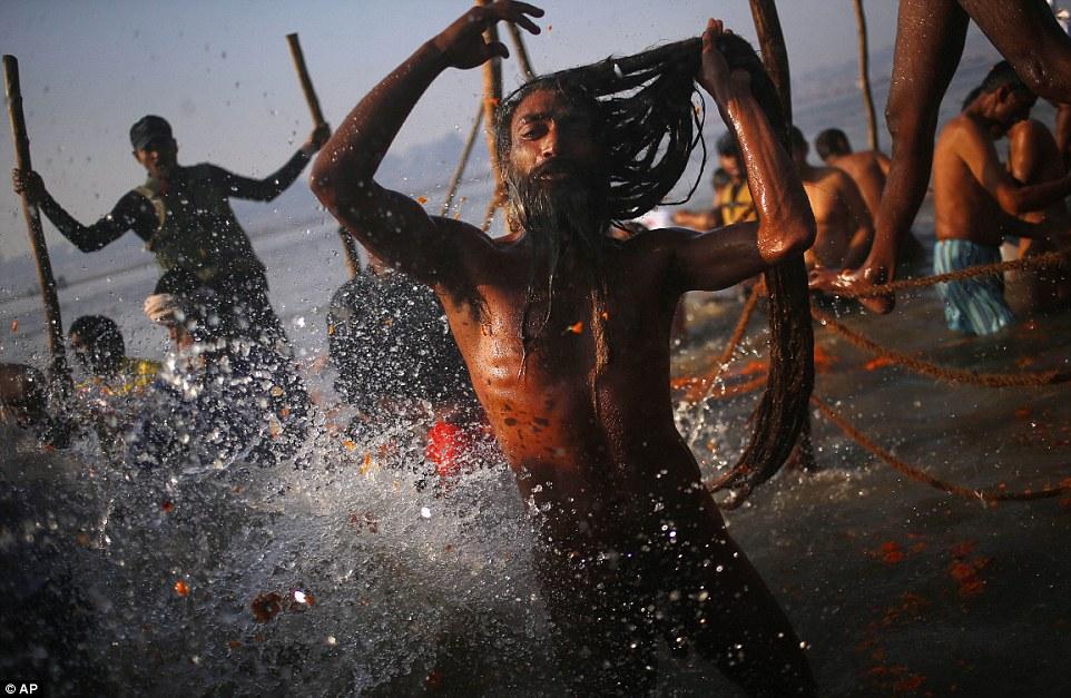 Купание: индус берет окунуться в переполненной водой во время фестиваля
