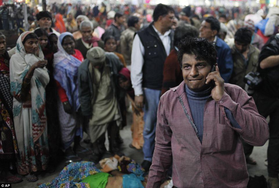 Разрушительные: индийские переговоры человеком по телефону, рядом с телом его родственник, который был убит в давке