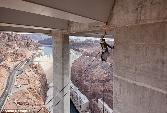 High up: The bridge inspectors were photographed 840 feet above the river