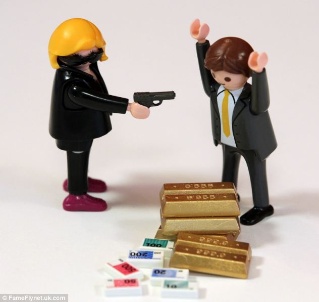 The blonde-haired doll points a gun at the bank manager as he hands over the gold bullion in the Playmobil Bank and Safe set which re-enacts a bank robbery