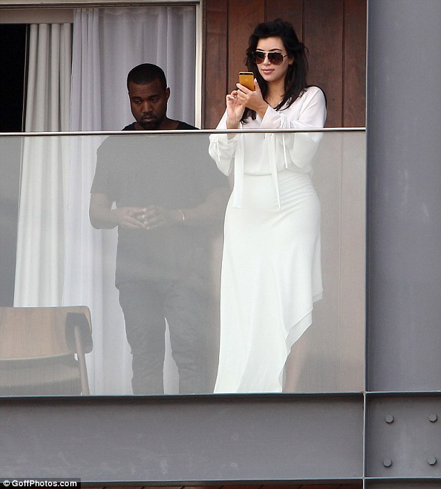 Would you rather be somewhere else? Kanye looks rather bored as Kim snaps photos for her album