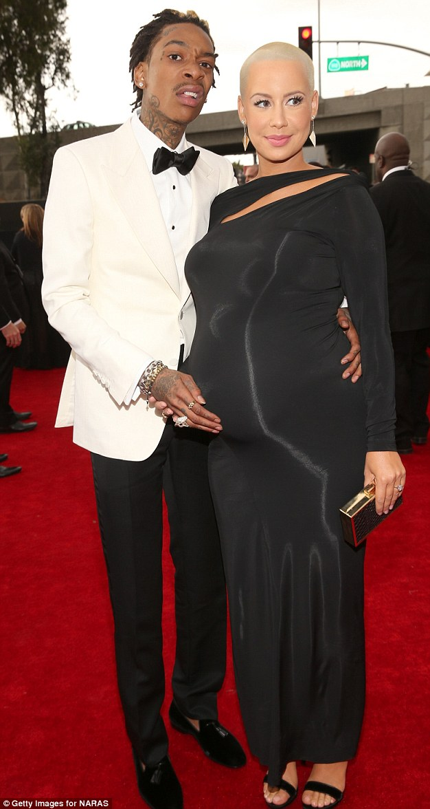 Huh? Wiz pulls a funny face as his fiancee smiles demurely, blithely unaware of her partner's antics