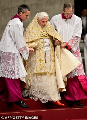 Pope Benedict XVI is helped by assistants as he celebrates the Vespers and Te Deum prayers in Saint Peter's Basilica at the Vatican on December 31, 2012