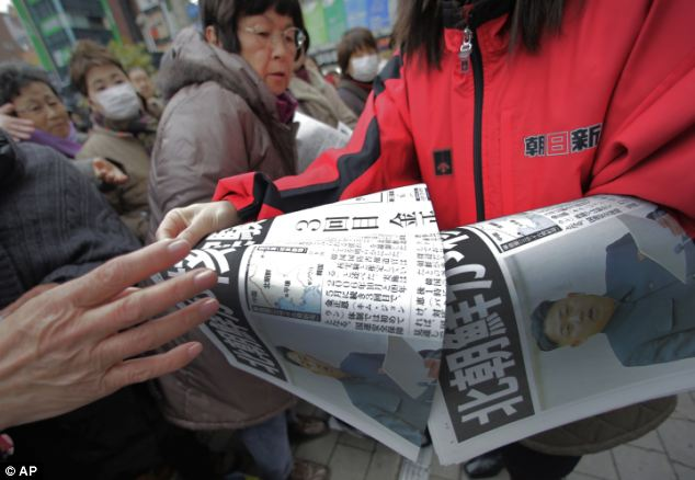 International attention: A passer-by prepares to pick up an extra edition of a Japanese newspaper reporting a nuclear test conducted by North Korea,
