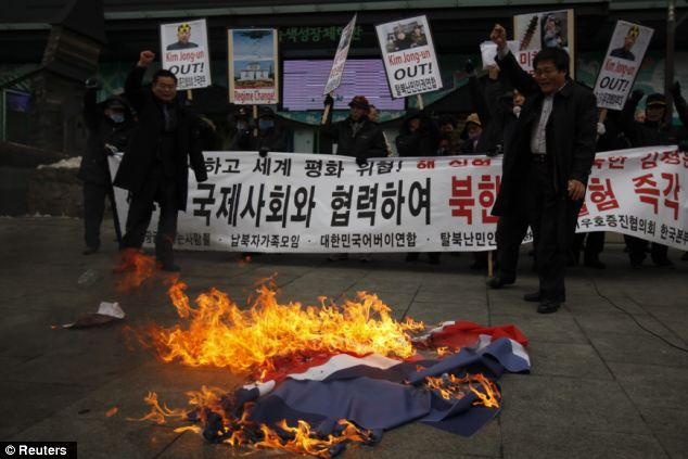 Burning: Activists from an anti-North Korea civic group burn a North Korea flag in front of banners bearing anti-North Korea messages near the U.S. embassy in central Seoul