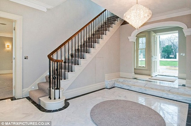 Luxury living: The house features lighting along the staircase, chandeliers and marble flooring
