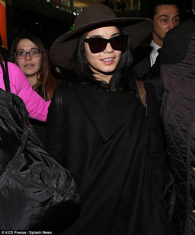 Boho babe: Vanessa Hudgens looked stylish in a large felt hat and a warp cape jacket