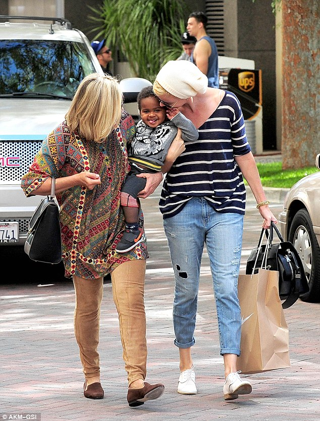 Birthday boy! Charlize Theron cuddles baby son Jackson while out shopping ahead of the tiny tot's first birthday party