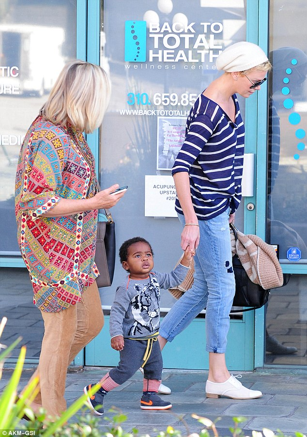 What's that mummy? Charlize's adopted son looks in wonder at something as he shops with his mum and grandmother
