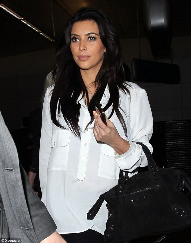 Hiding her bump: A fresh-faced Kim wore a white shirt that covered her pregnancy curves