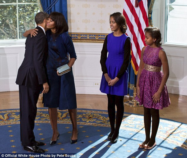 Happy occasion: President Obama and Michelle embrace following the official swearing-in ceremony in the Blue Room of the White House while their daughters Malia and Sasha look on