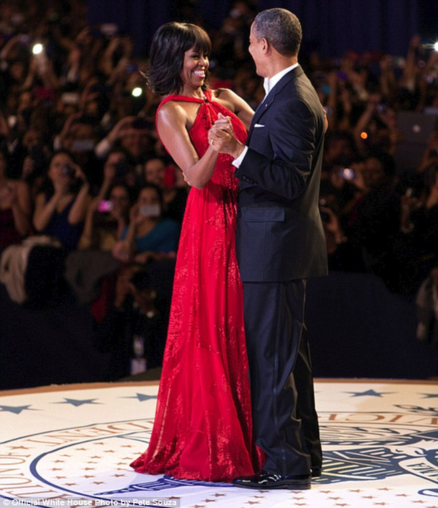 Dressed for the occasion: Mrs Obama debuted a stunning red gown by designer Jason Wu as she joined her husband onstage for their first inaugural dance