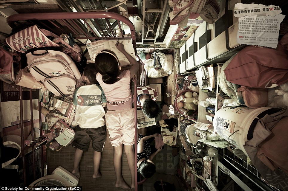 Like battery hens: A family of four tries to get on with everyday life despite living in a room where there is barely space to move in the urban slums of Hong Kong