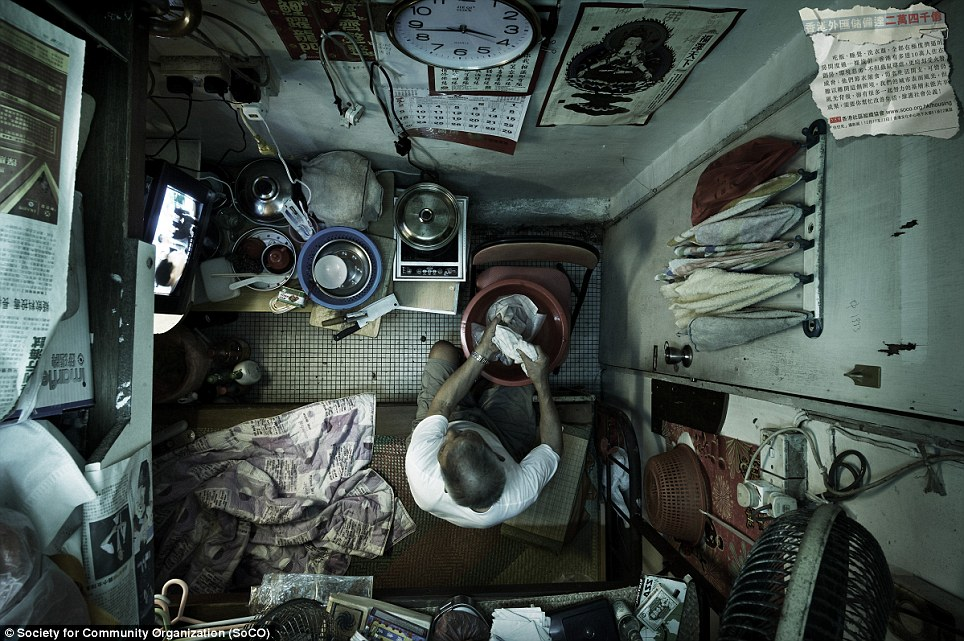 Utility room: A man washes his clothes while sitting on his bed next to his 'kitchen'. Hundreds of thousands of people still live in caged homes like this in Hong Kong
