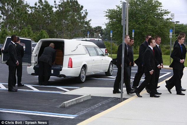 Solemn Duty: A white hearse, escorted by two police cars, delivered the singer's wooden casket to the service and took her to be buried nearby