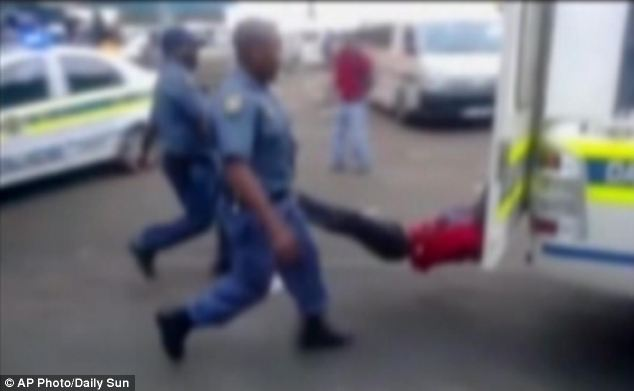 In this still frame, taxi driver Mida Macia is shown being dragged along the road by a moving police van, with his limbs carried by officers
