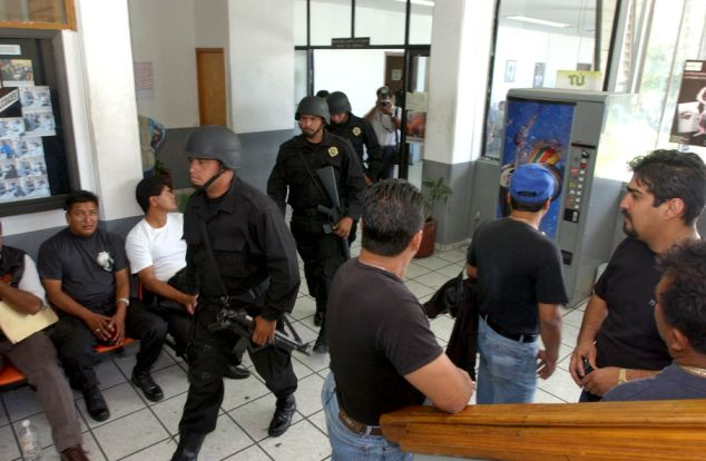 Violence: Heavily armed police patrol the attorney general's office in Morelos, Mexico, where the body of child hitman Jorge Armando Moreno, 13, was found tortured and dumped alongside five other murder victims today