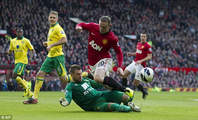 Beaten to the punch: Rooney is sent flying by Mark Bunn (left) after the Norwich keeper slid in