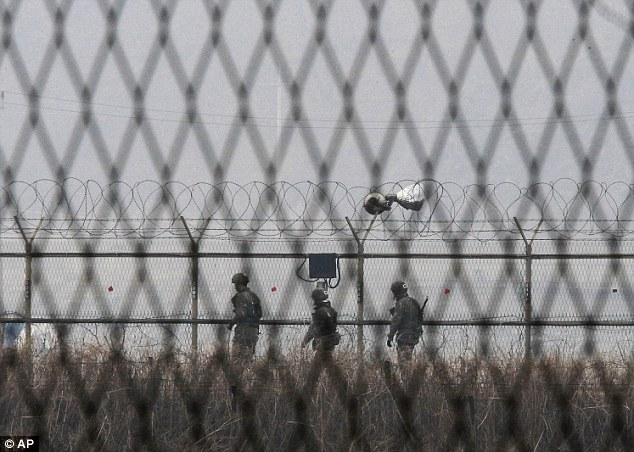 Uneasy truce: South Korean Army soldiers patrol along a barbed-wire fence near the border village of Panmunjom in Paju, South Korea