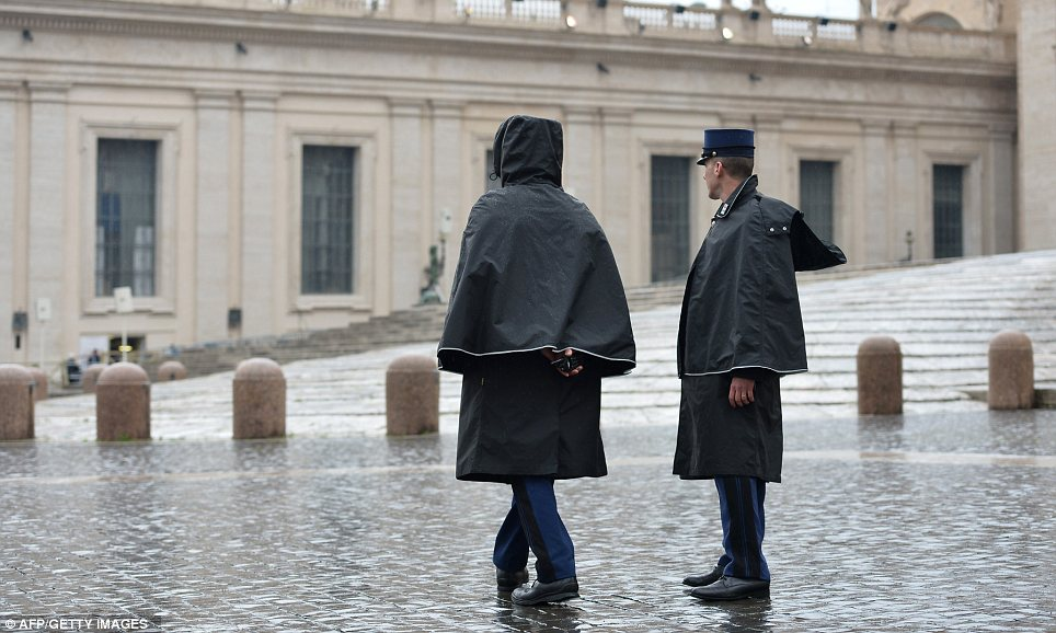 On duty: Even the Vatican gendarmes had to cover up to defend against the weather in St Peter's Square