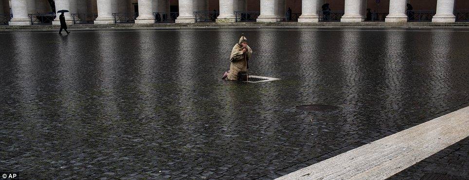 Pilgrim: A man kneels in prayer in a rain-slicked St Peter's Square while cardinals gather in the chapel