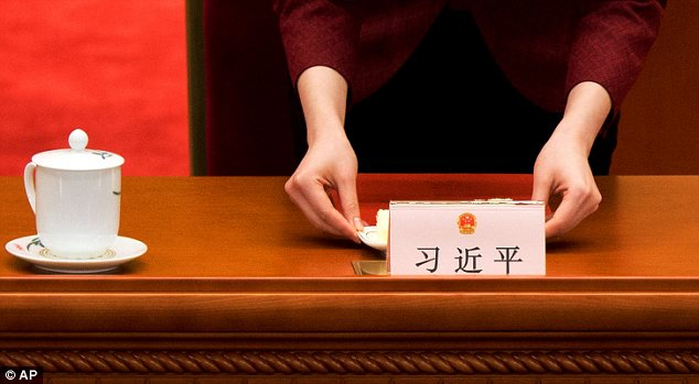 Setting the scene: A hostess arranges Xi's seat before the start of Thursday's session