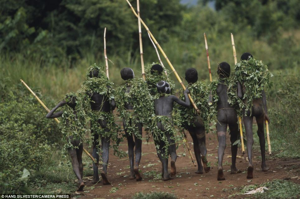 Camouflaged: A group of children disguise themselves with vegetation for a hunting trip near their African home
