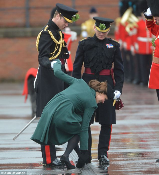 Keeping her cool: Kate laughs off the embarrassment as she tries to tug her four inch heel from the grate