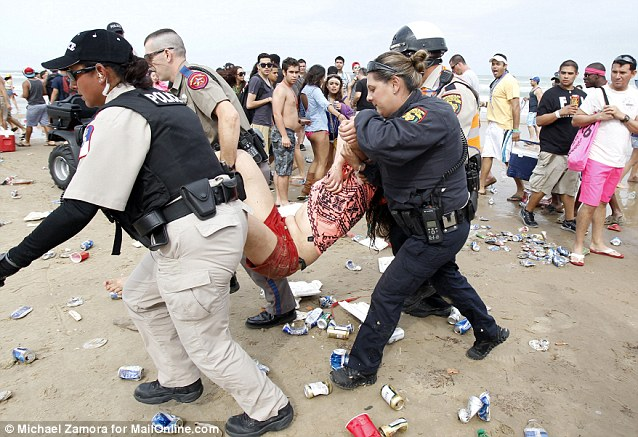 Police officers haul off a severely intoxicated girl and rush her away for treatment