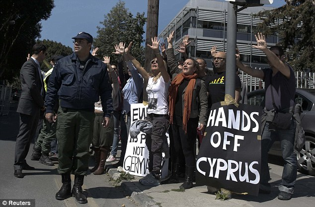 Hands off: Demonstrators protest as Cypriot President Nicos Anastasiades's convoy drives to parliament in Nicosia
