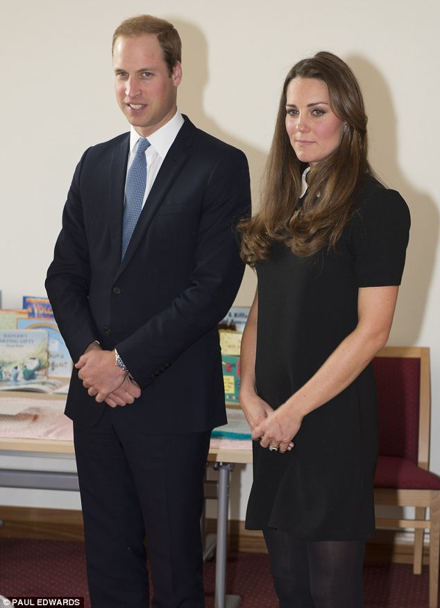 Kate places her hands gently on her bump, which was just starting to show underneath her Topshop dress