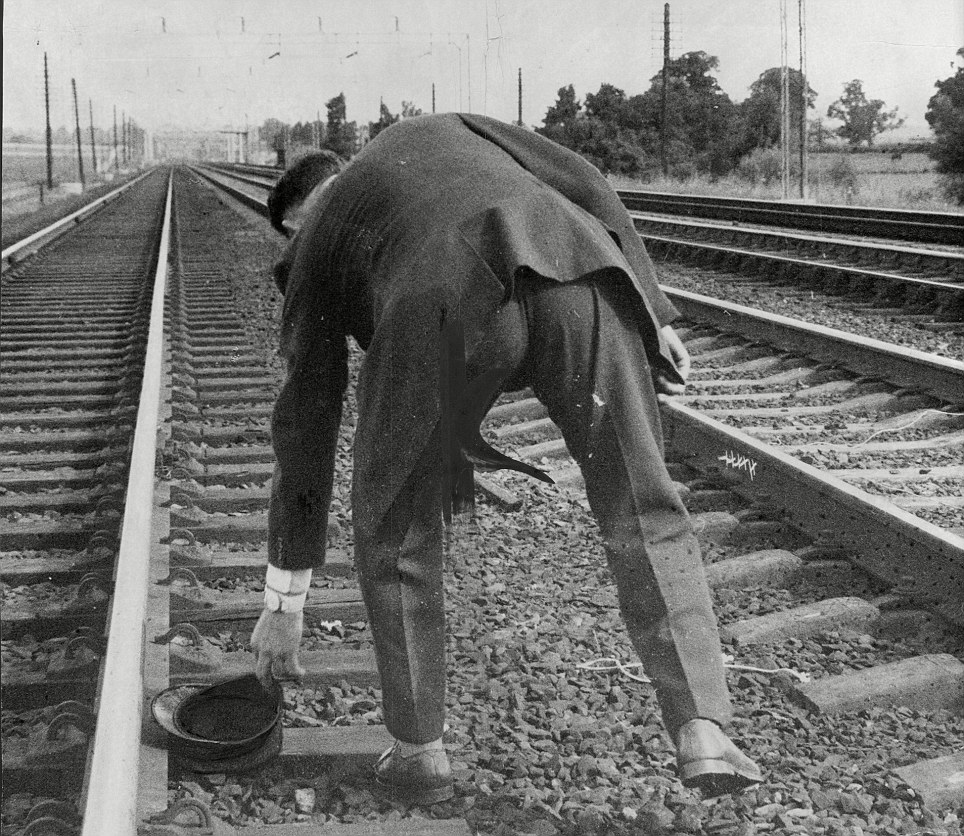 Investigation: A policeman picks up the train driver's hat from the railway tracks near the ambush site