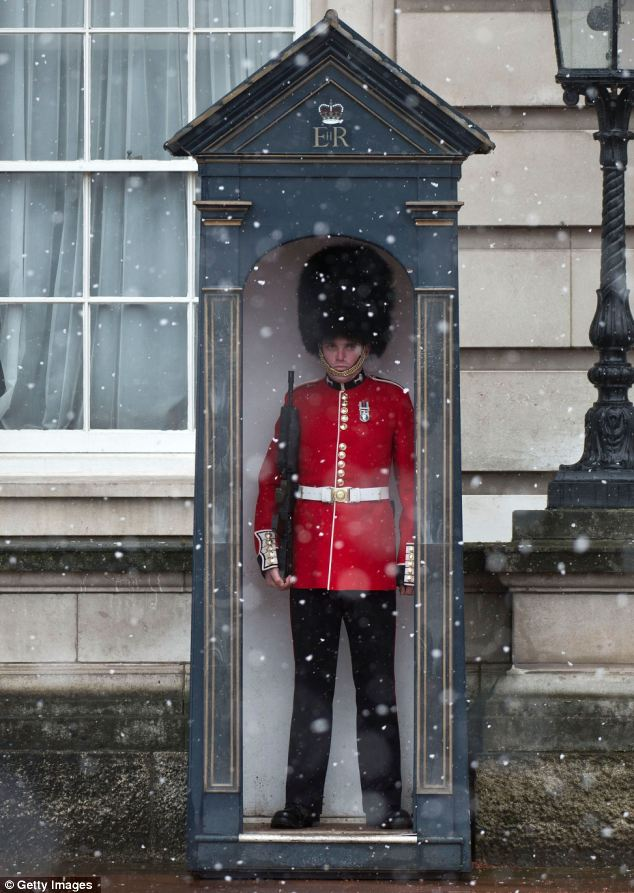A soldier stands on guard during a snow shower on the first day the soldiers are wearing their summer red tunics outside Buckingham Palace