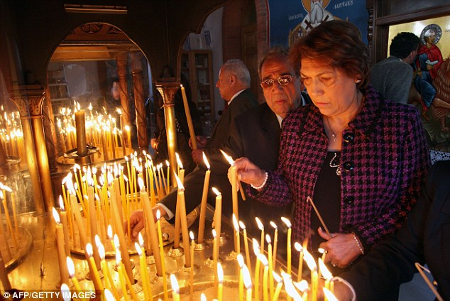 Religious observance: Cypriots light candles during a service at Saint-Mamas Orthodox church in Nicosia