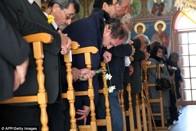 Saying their prayers: Cypriots attend a Sunday service at Saint-Mamas Orthodox church in Nicosia