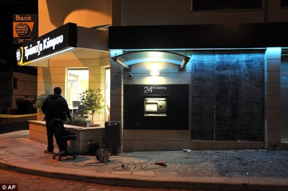 Country in turmoil: A worker restores a damaged door of a branch of a Bank of Cyprus in the early hours of Monday after a bomb attack at Polemidia, a suburb of the southern port city of Limassol