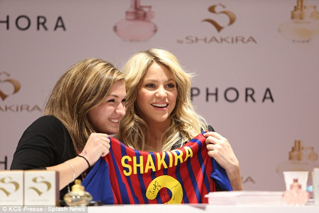 How cool! Shakira looked chuffed as she posed with a fan's football jersey that featured the star's name on the back