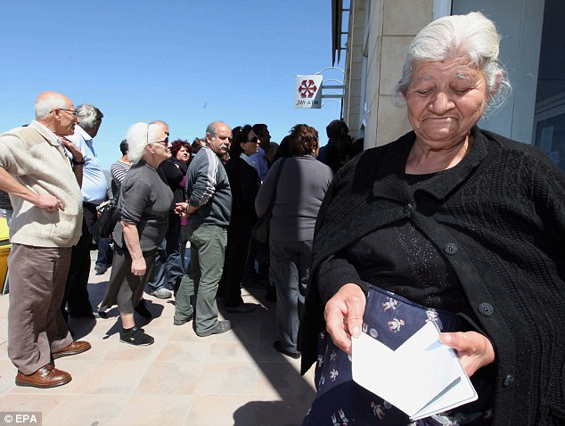 Uncertainty: An elderly woman looks at a savings book as people wait in line in front of a branch of the Laiki Bank in Nicosia, Cyprus