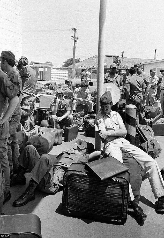 Bored: In this March 27, 1973 photo, an American GI takes a nap atop his luggage as he and other troops wait to begin out processing at Camp Alpha in Saigon