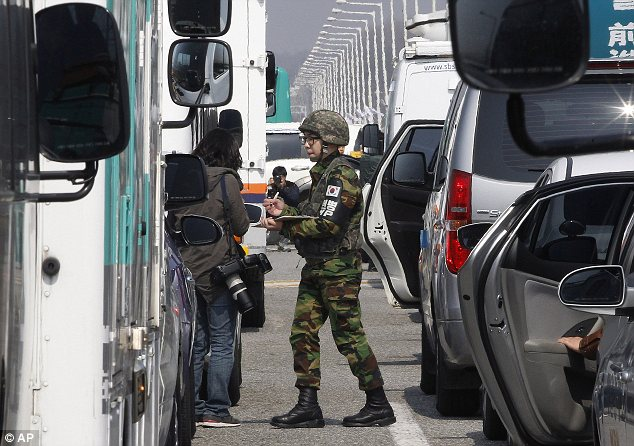 Checkpoint: A South Korean soldier checks credentials in the middle of the traffic jam near the border