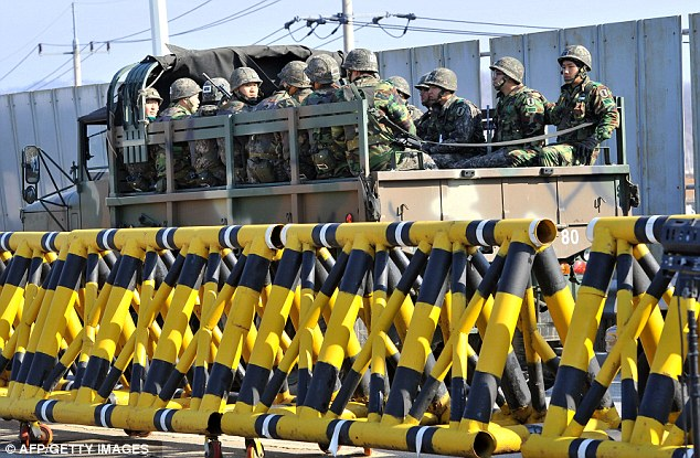 Mobilising: South Korean soldiers ride a military truck on the road leading to North Korea at a military checkpoint in the border city of Paju