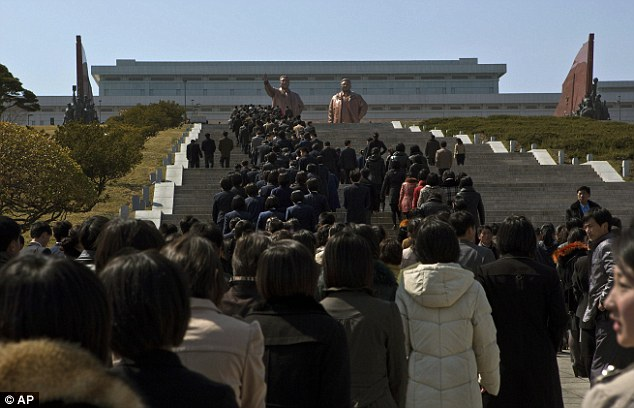 Young North Korean workers and students climb stairs to the base of bronze statues of the late leaders Kim Il Sung and Kim Jong Il during an event to pledge loyalty to the country in Pyongyang