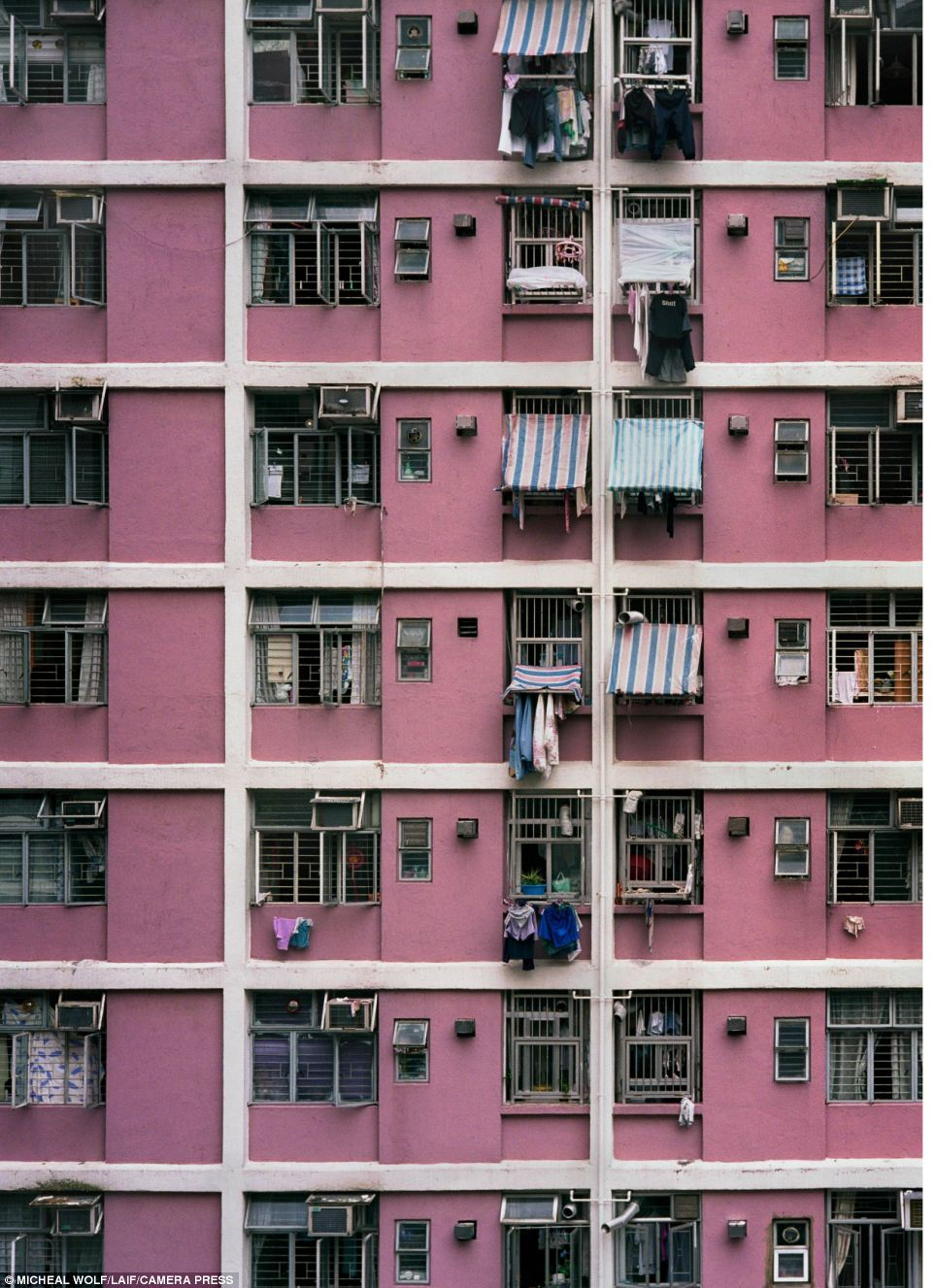 Hong Kong: Laundry hangs from the barred windows of this tower block, the walls of which are painted pastel pink