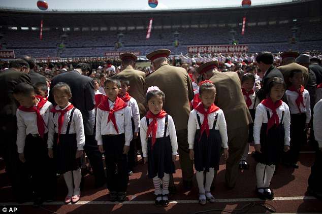 First steps into tyranny: North Korean children stand waiting while officers tie red bandanas around their necks during a ceremony to induct them into the Korean Children's Union
