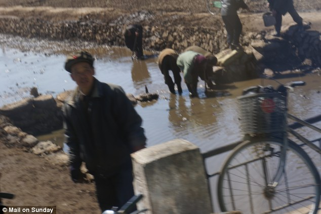 Daily grind: Peasants working in a stream in a countryside that resembles a moonscape