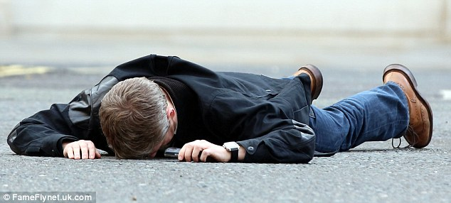 Out for the count: Martin Freeman lies face down on the pavement, totally motionless