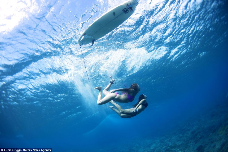 Clear blue sea: Two surfers glide effortlessly under the turbulent sea as they look for the perfect wave to ride in the Volcom Pro competition